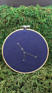 Embroidery of the zodiac constellation Cancer on navy blue fabric in an embroidery hoop.