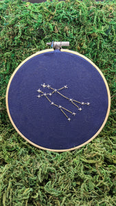 Embroidery of the zodiac constellation Gemini on navy blue fabric in an embroidery hoop.