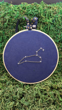Load image into Gallery viewer, Embroidery of the zodiac constellation Leo on navy blue fabric in an embroidery hoop.