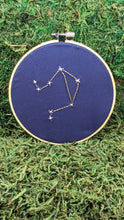 Load image into Gallery viewer, Embroidery of the zodiac constellation Libra on navy blue fabric in an embroidery hoop.