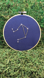 Embroidery of the zodiac constellation Libra on navy blue fabric in an embroidery hoop.