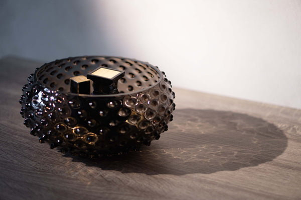 Black Smoke Glass Hobnail Bowl with parfumes in it on the table