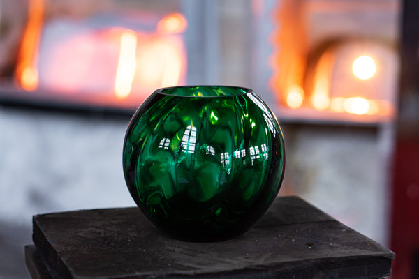 Dark Green Marika Round Vase standing in front of a glass furnace