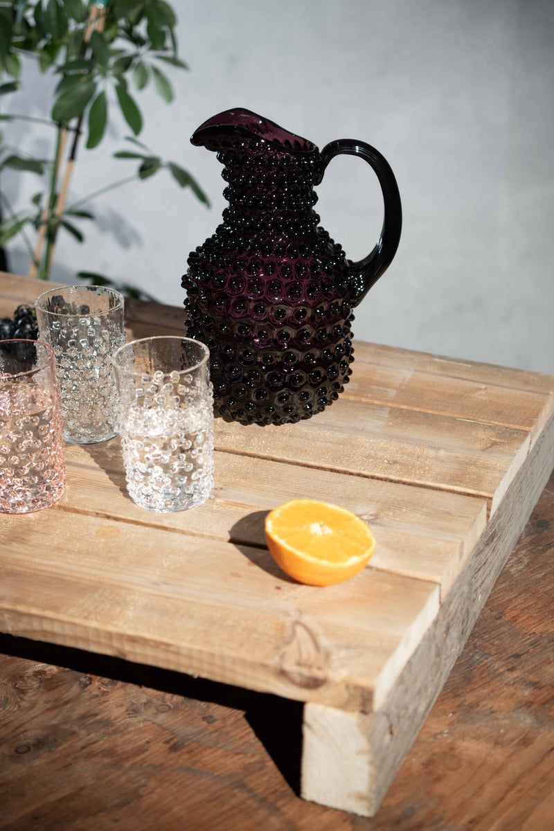 Hobnail square jug in Violet with two crystal hobnail tumblers and one rosaline tumblers on a wooden table with a half of orange in front of the glassware and a plant behind it