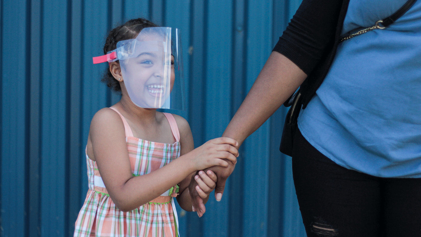 A young girl holding her mother's hand and smiling as she wears a Kids face shield from The Canadian Shield.