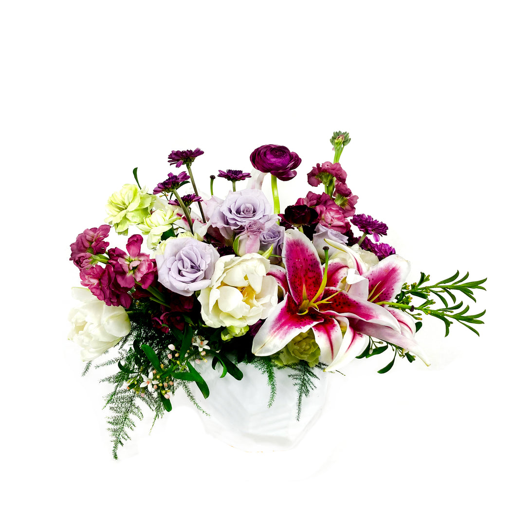 Purple, lavender, and white flowers sit in a delicate vase against a white background