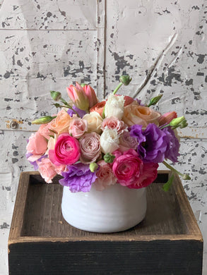 Floral arrangement of tulips, roses, ranunculas, and stock in ceramic bowl
