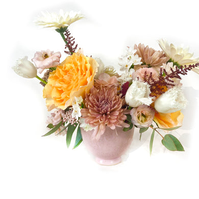A pink vase holds pastel roses, white and orange flowers, and greenery against a white background