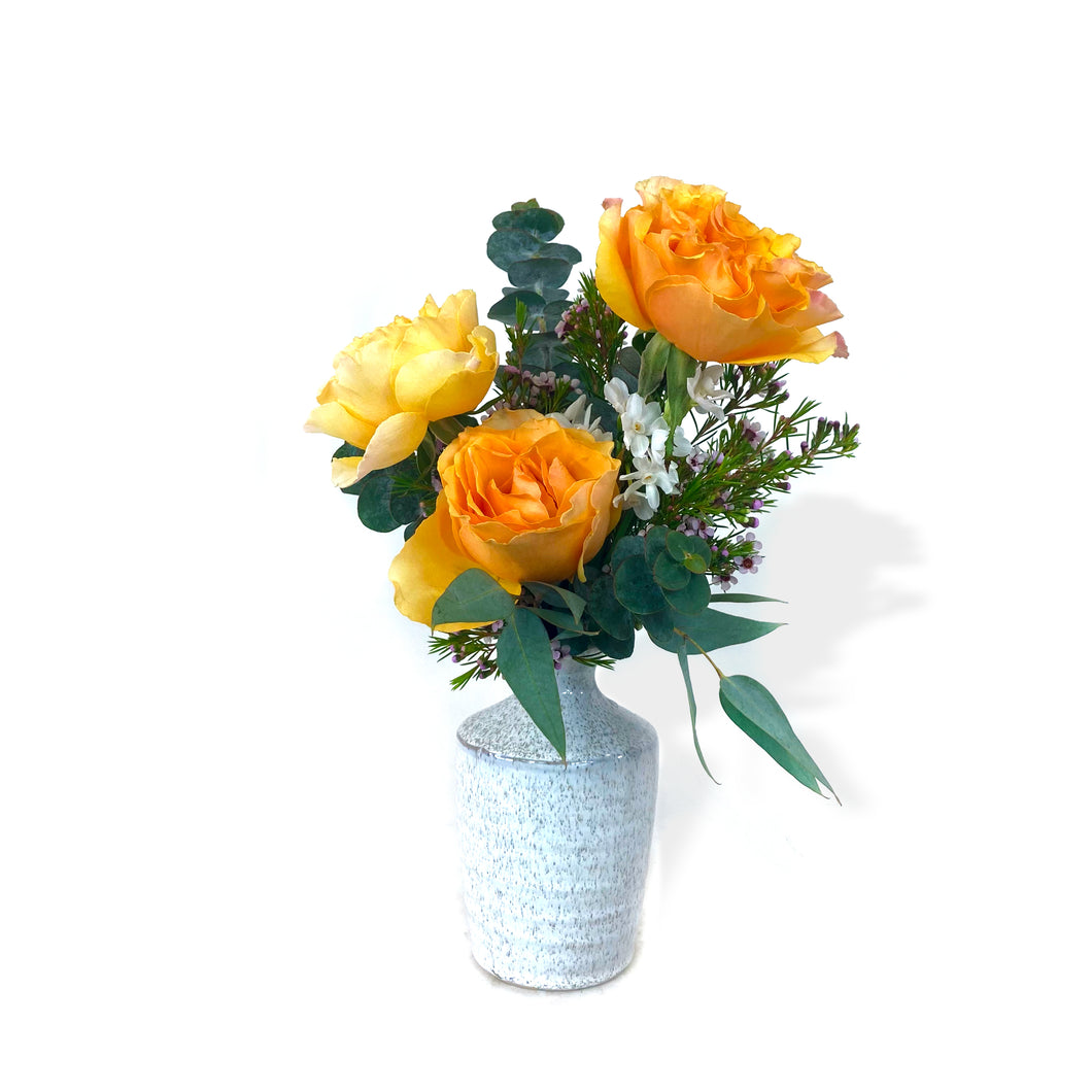 A white speckled vase holds orange and white flowers, complete with greenery, against a white background