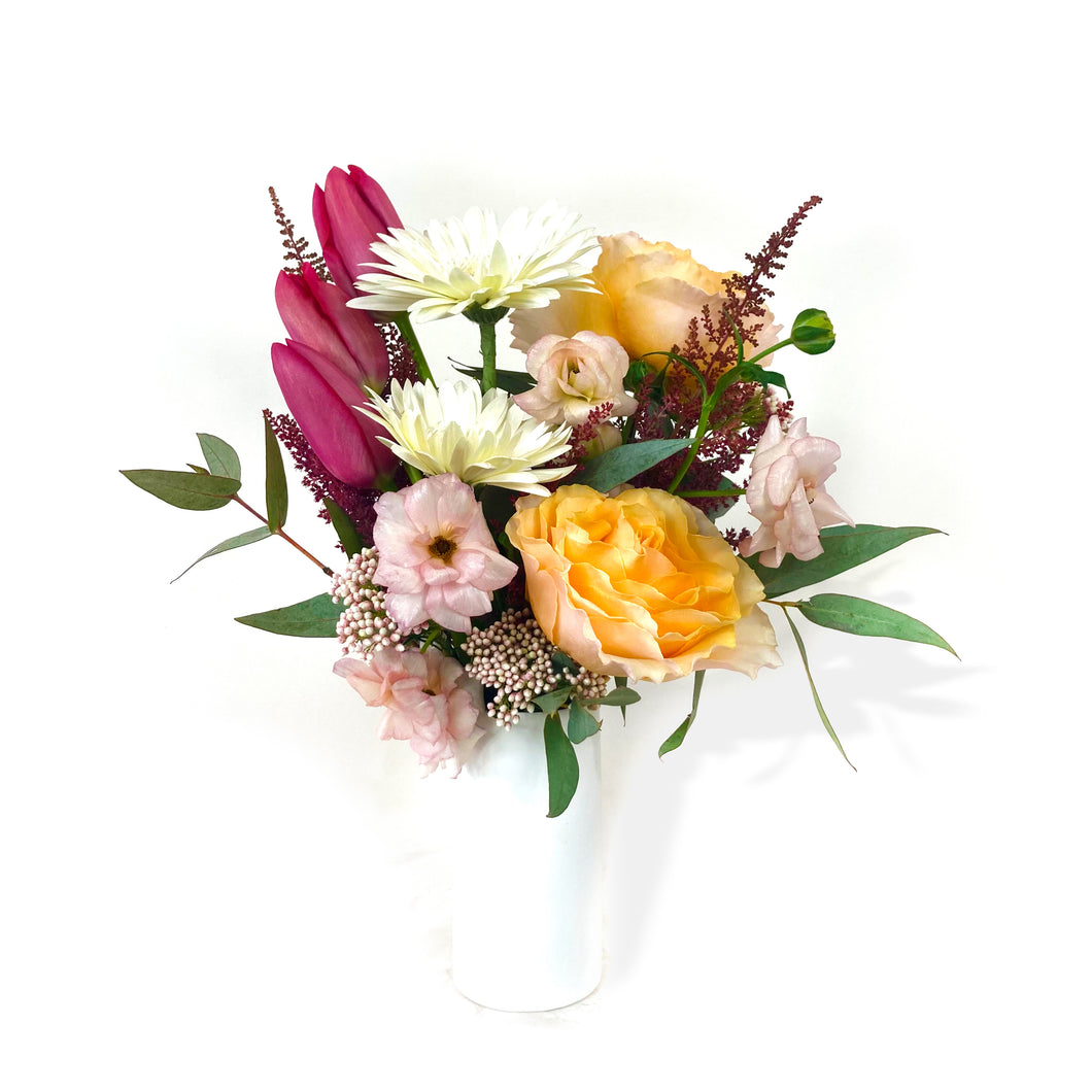 A white vase holds soft orange, purple, white, and pink flowers against a white background