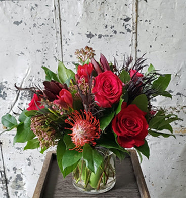 Red rose and protea floral arrangement in glass vase