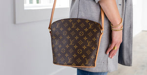 Woman wearing a Louis Vuitton handbag on her shoulder.