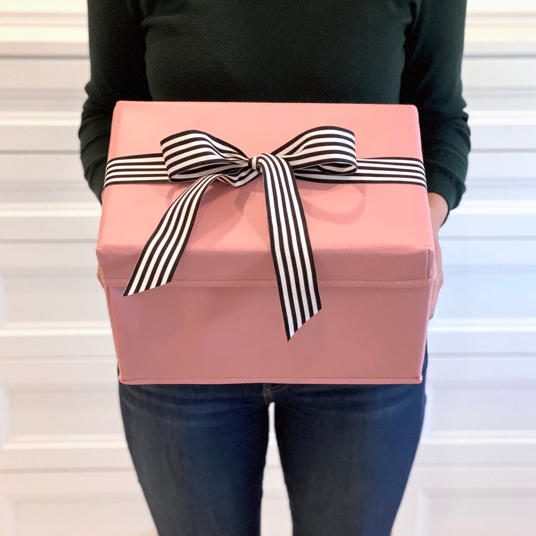 Small shoebox sized pink collapsible gift box with black and white grosgrain ribbon attached, great zero waste solution for sustainable and eco-friendly gift boxes