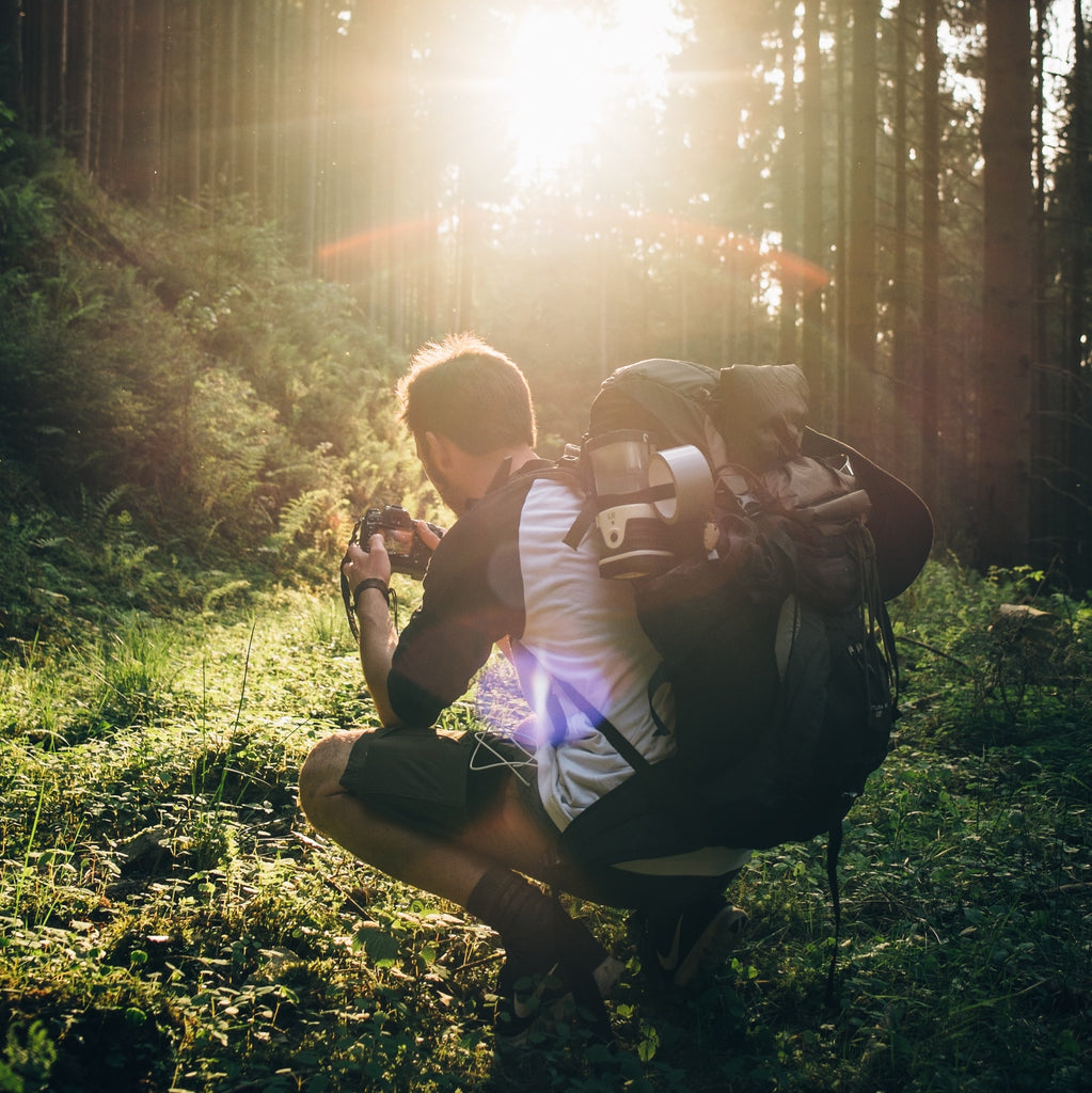 A man crouching down to get the perfect photo while backpacking through the forest