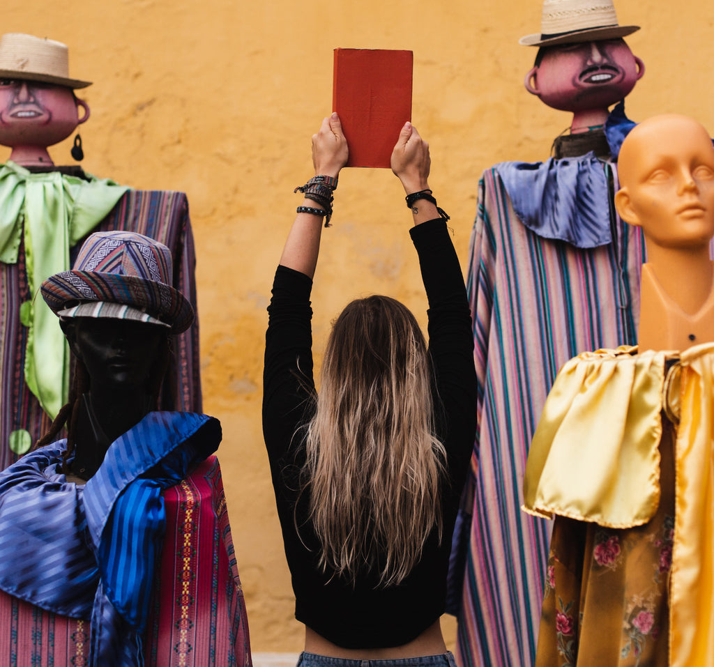 A girl holds up the Wakeful Travel Journal in the middle of four mannequins in Guatemala