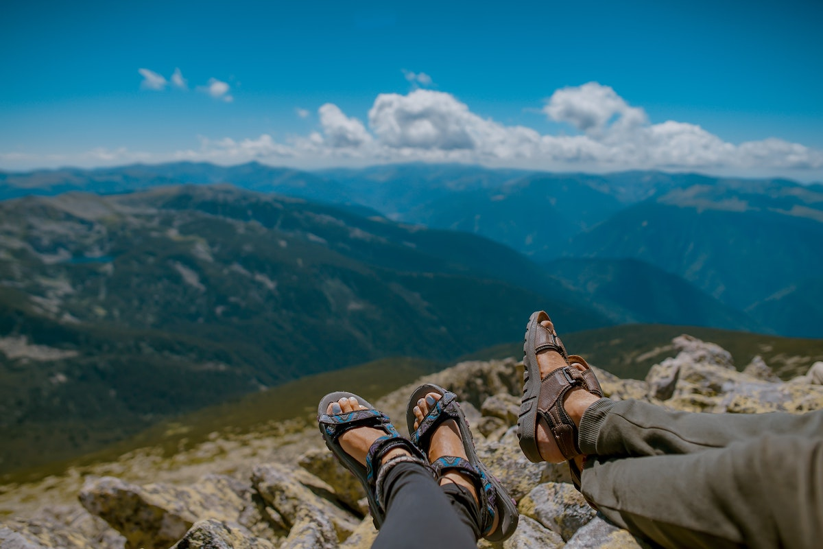two people's feet in hiking sandles looking out into a mountain valley