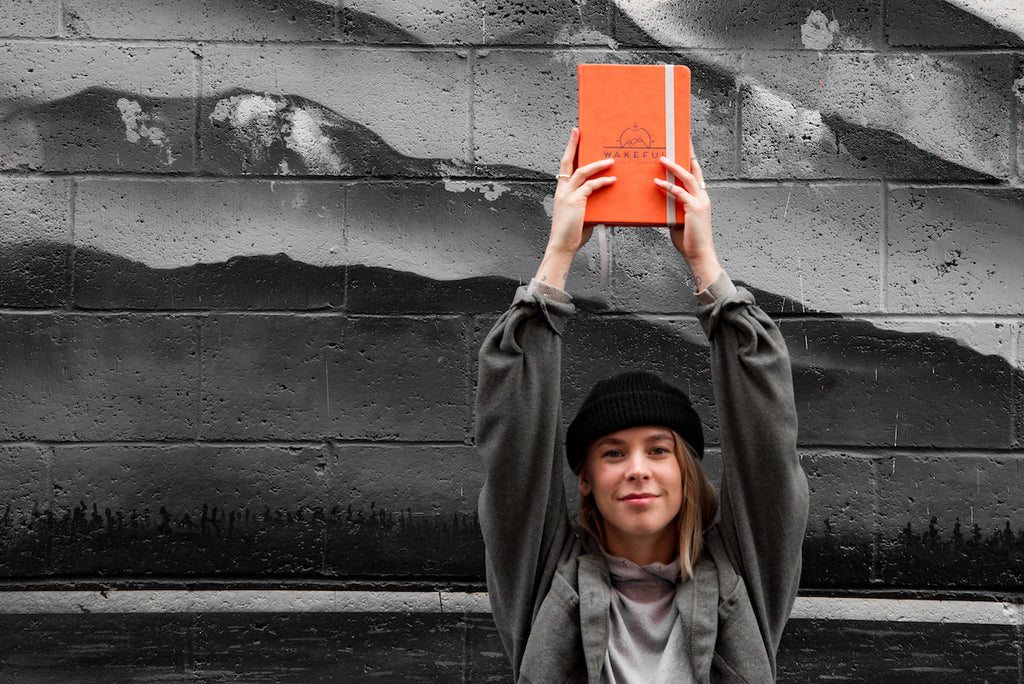blonde woman holding up a mindful travel journal