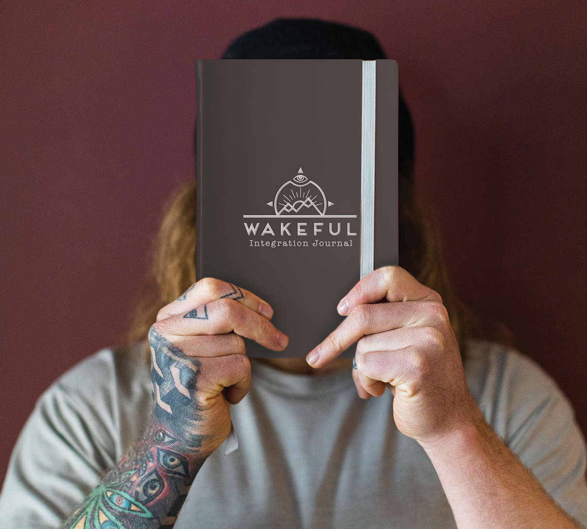 a man with tattoos and long hari holds up an integration journal over his face