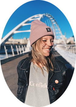 girl ion pink toque smiling near a big white bridge