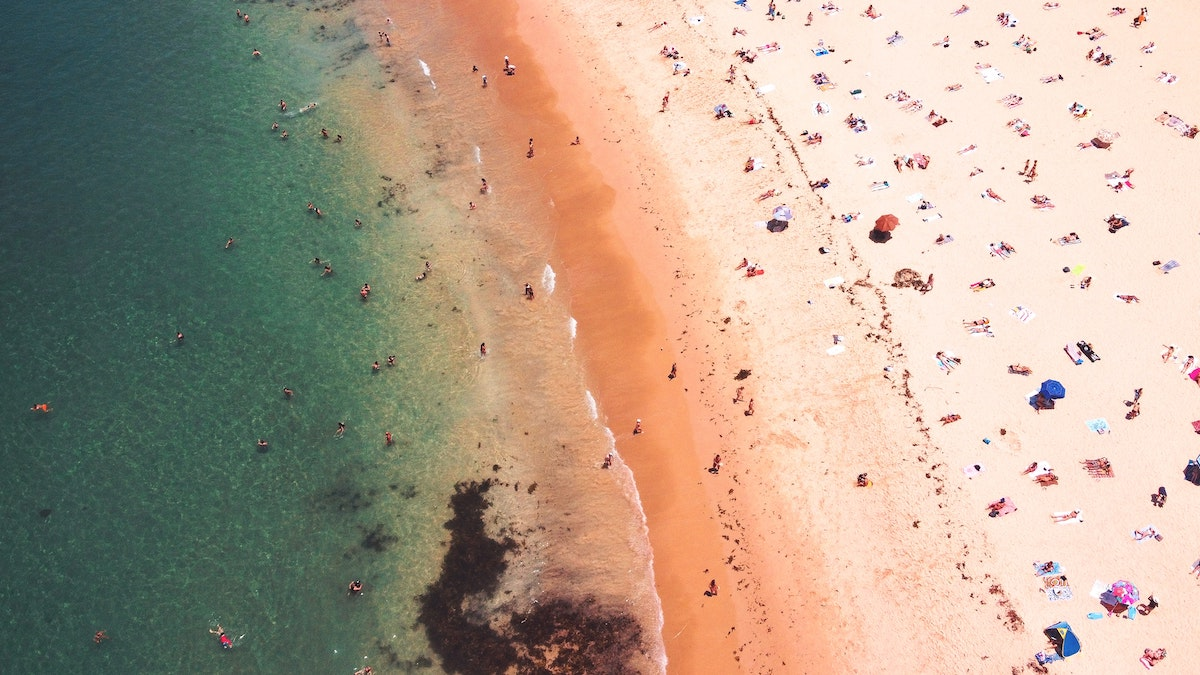 arial view of the blue ocean, shoreline and people scattered on Coogee Beach, Australia