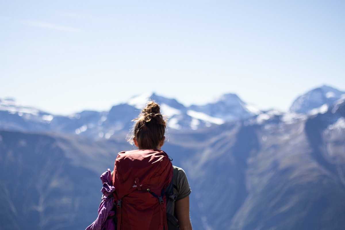 girl with a red backpack with her back faced away looking at snowy mountains