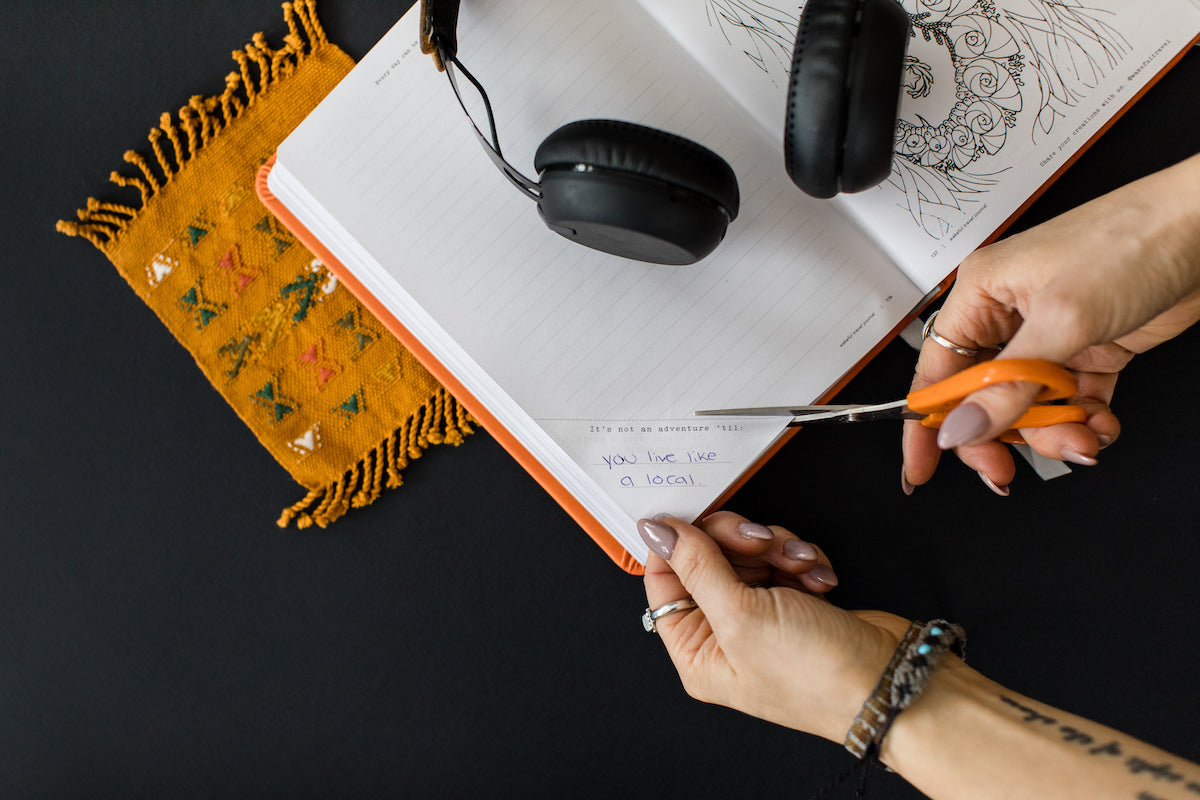 someone cutting a journal prompt out of a mindful travel journal