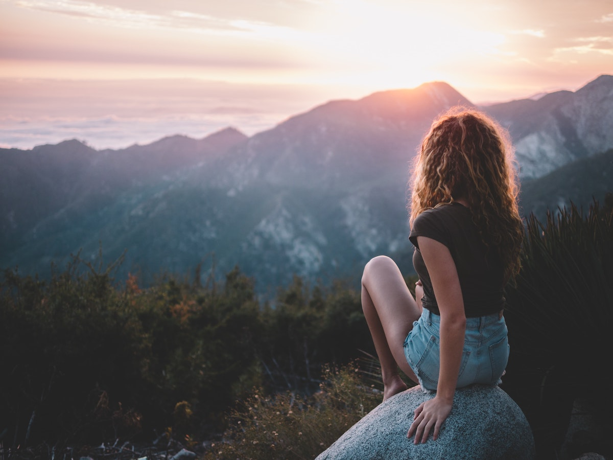 a woman sitting on a rock looking into the setting sun over the mountains