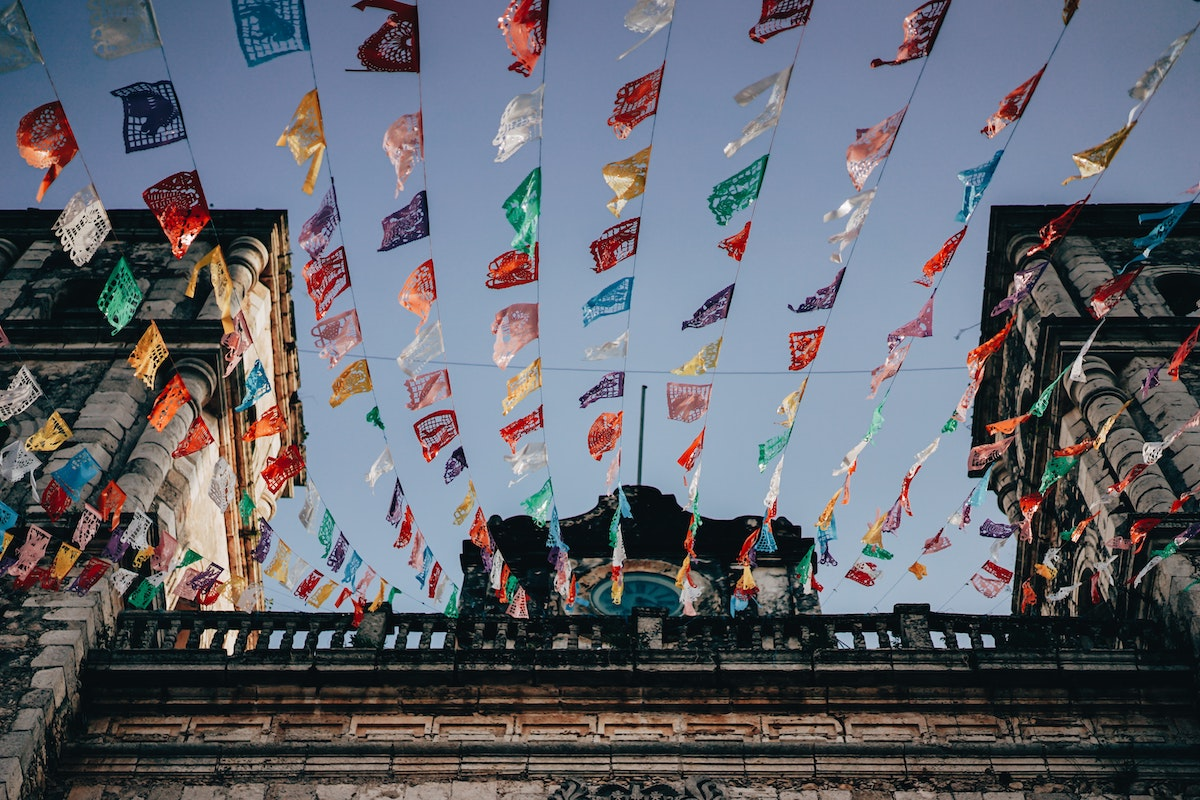 blue sky with lines of mexican flags hanging above