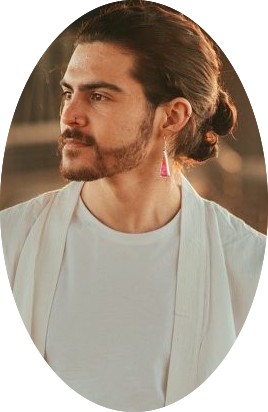 A man with a man-bun and beard dressed in white