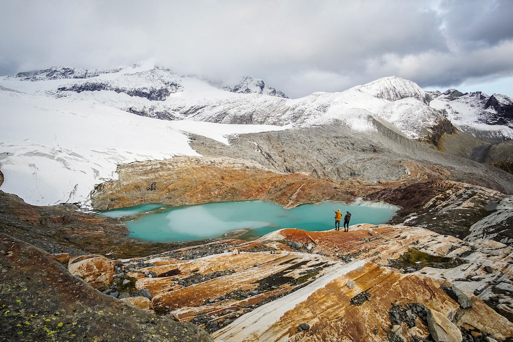 blue-green alpine lake surrounded by snowy mountains and two hikers below