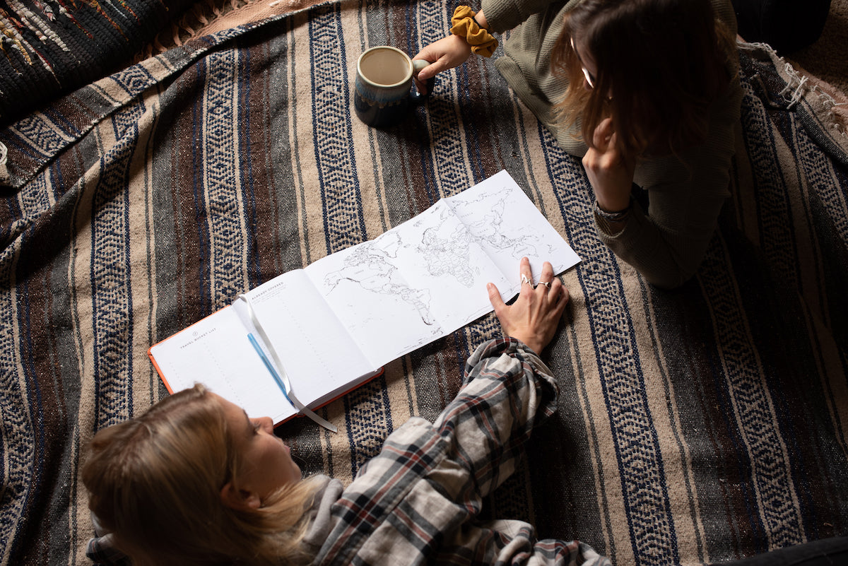 two girls laying on a rug pointing at the fold out map in a journal