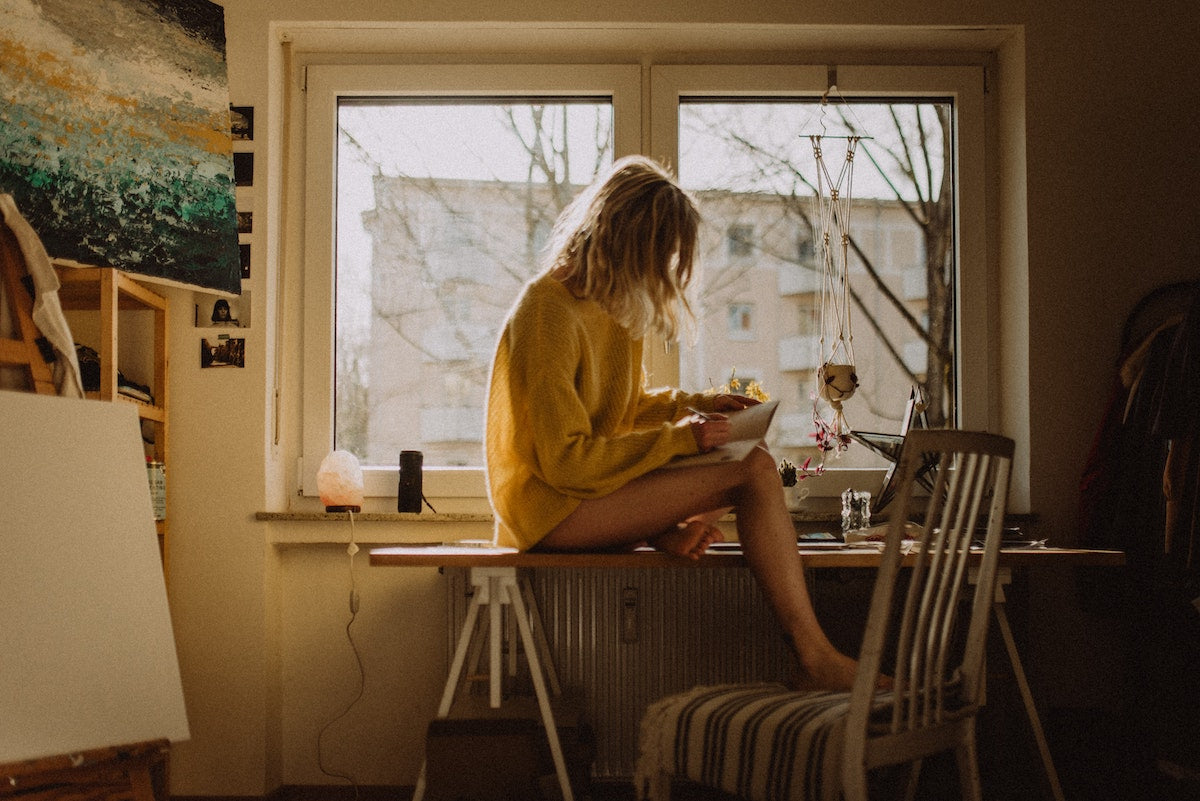 girl in oversized sweater journaling at kitchen table
