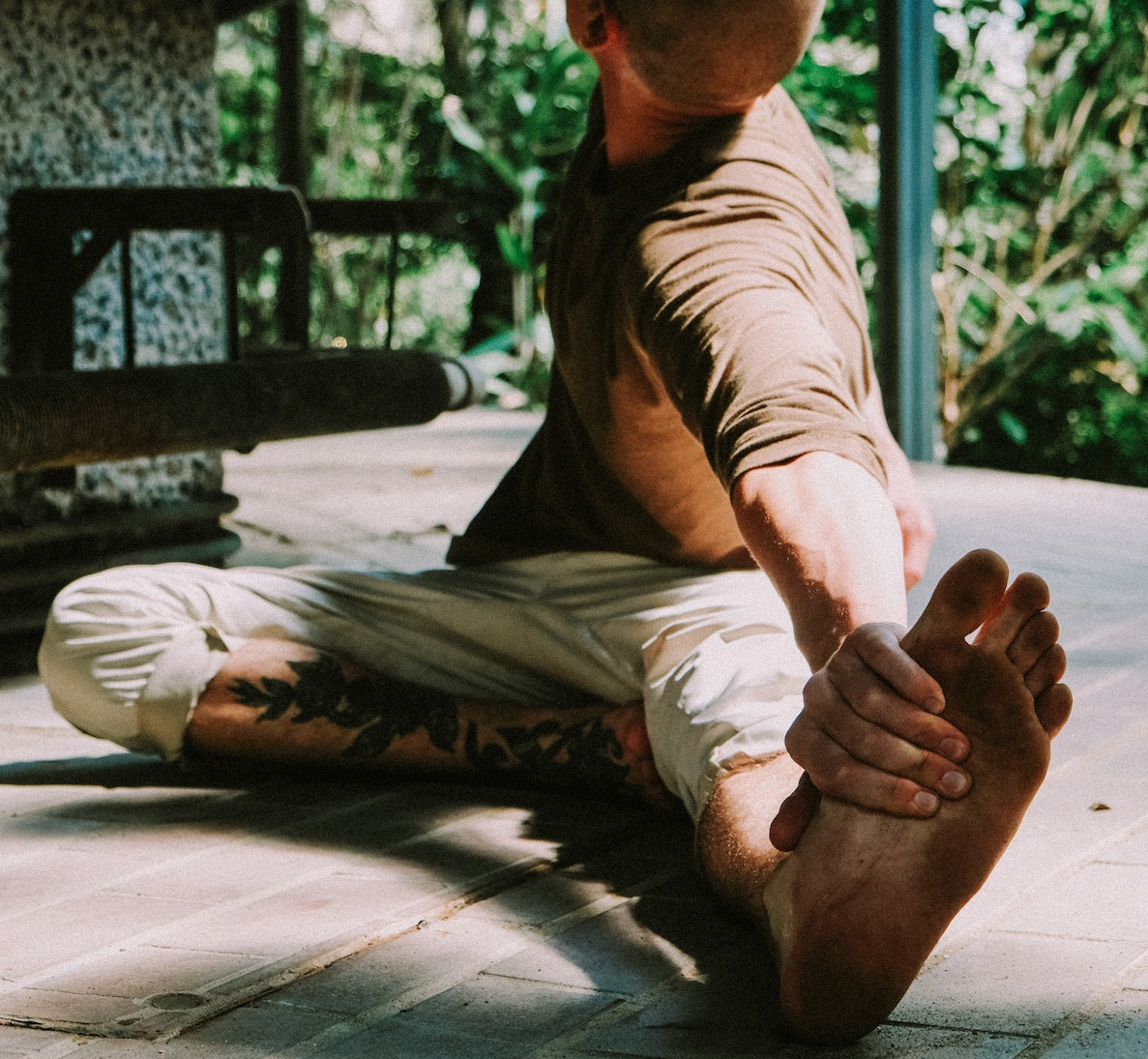 Man stretching in bare dirty feet