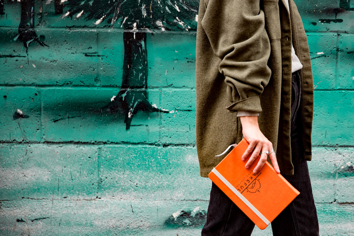 girl holding an orange mindful travel journal while walking past a mural