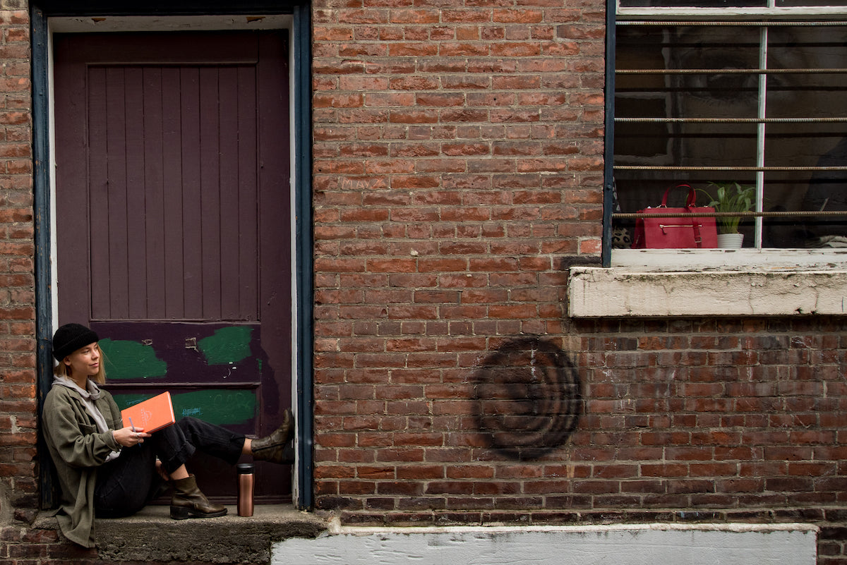 girl sitting in a back alley nook journaling