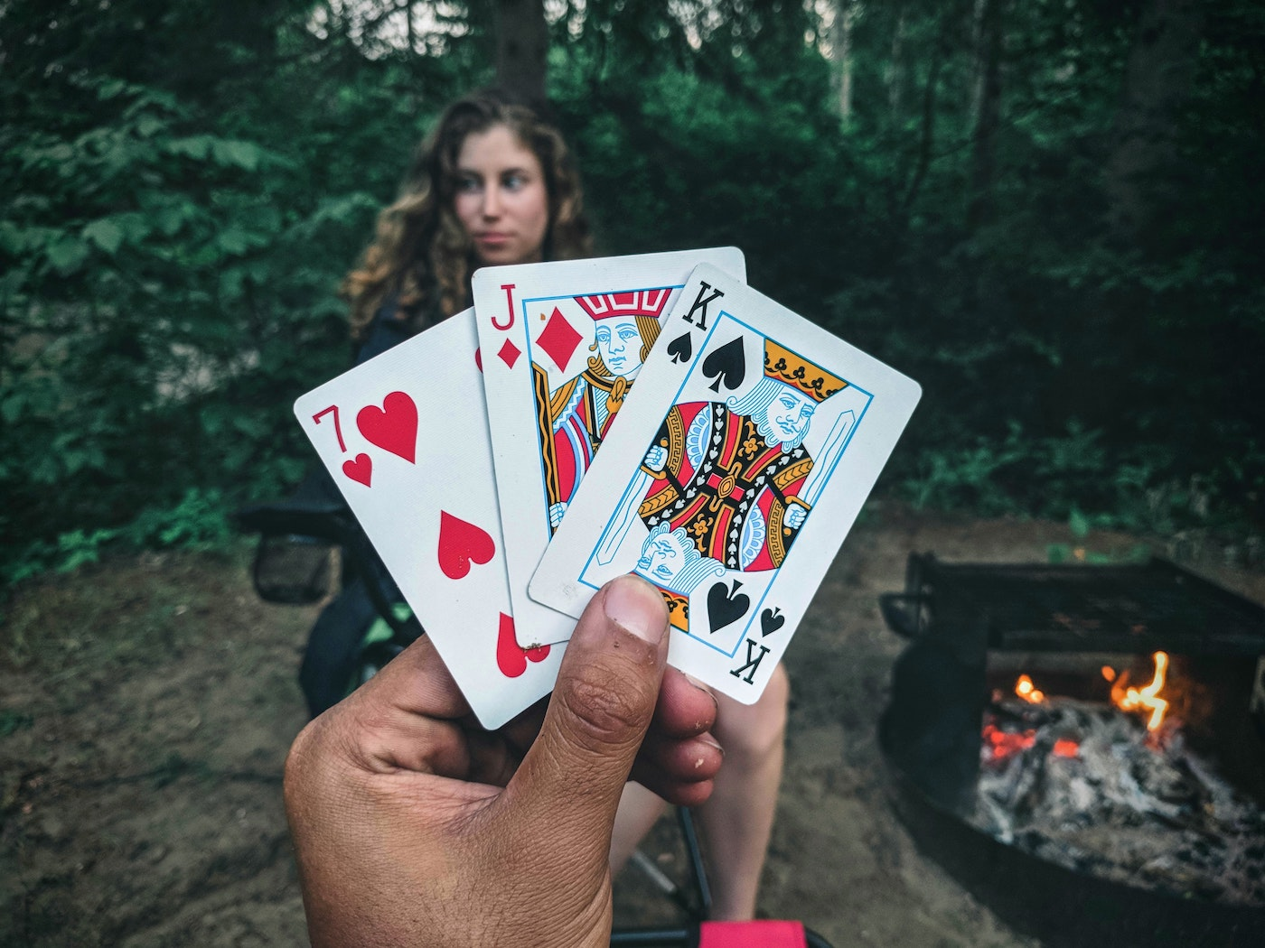 a man's hand holding three playing cards with a woman in the background
