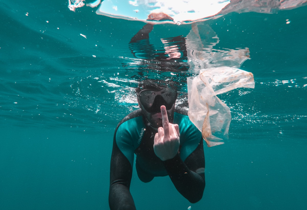 snorkler in the ocean giving the middle finger to camera while a plastic bag floats in front of him