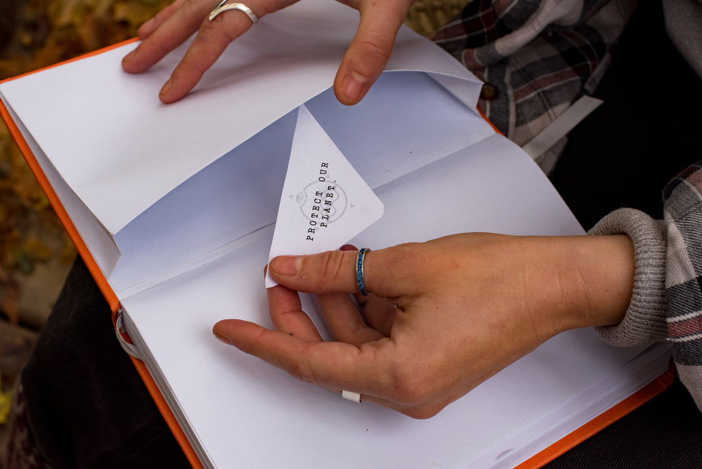 close up of girl putting piece of paper in the back pocket of the journal