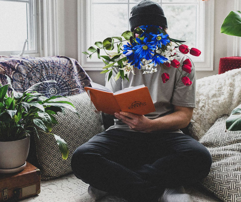 a man looking at his psychedelic integration book while flowers come out of his head.