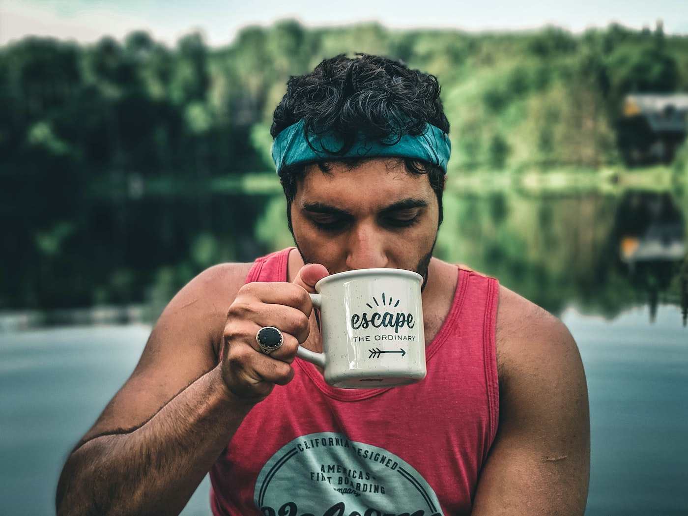 a man sipping coffee out of a camp cup with lake in the background