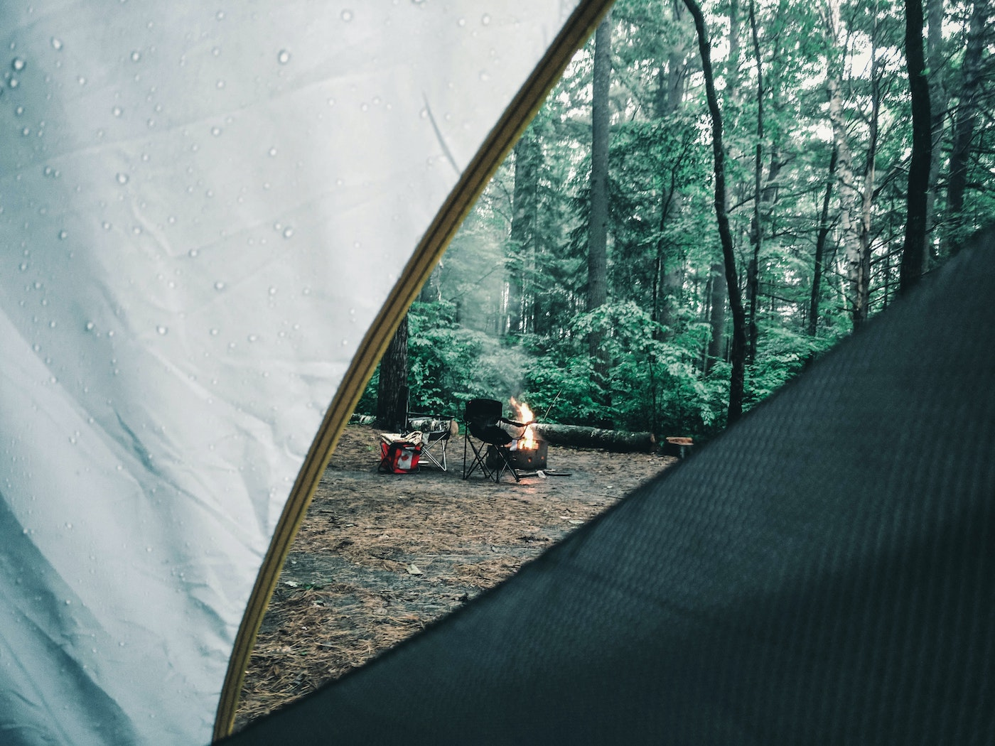 the inside of the tent, looking out at a campfire