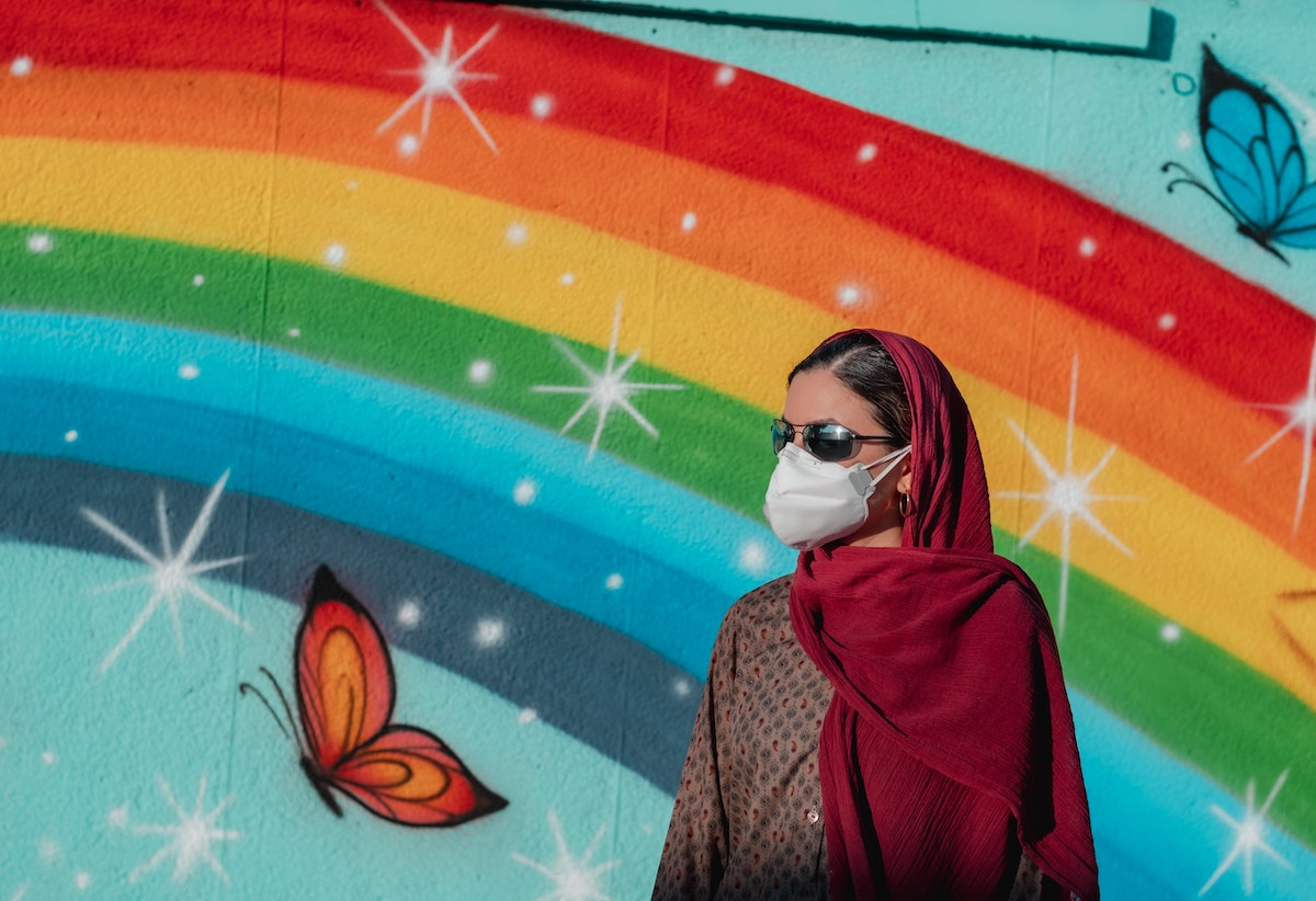 middle eastern women wearing a white mask in front of a rainbow mural painting