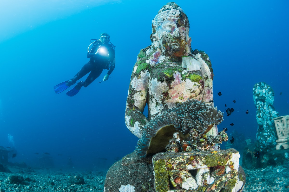 an underwater statue with a diver swimming behind in Bali, Indonesia