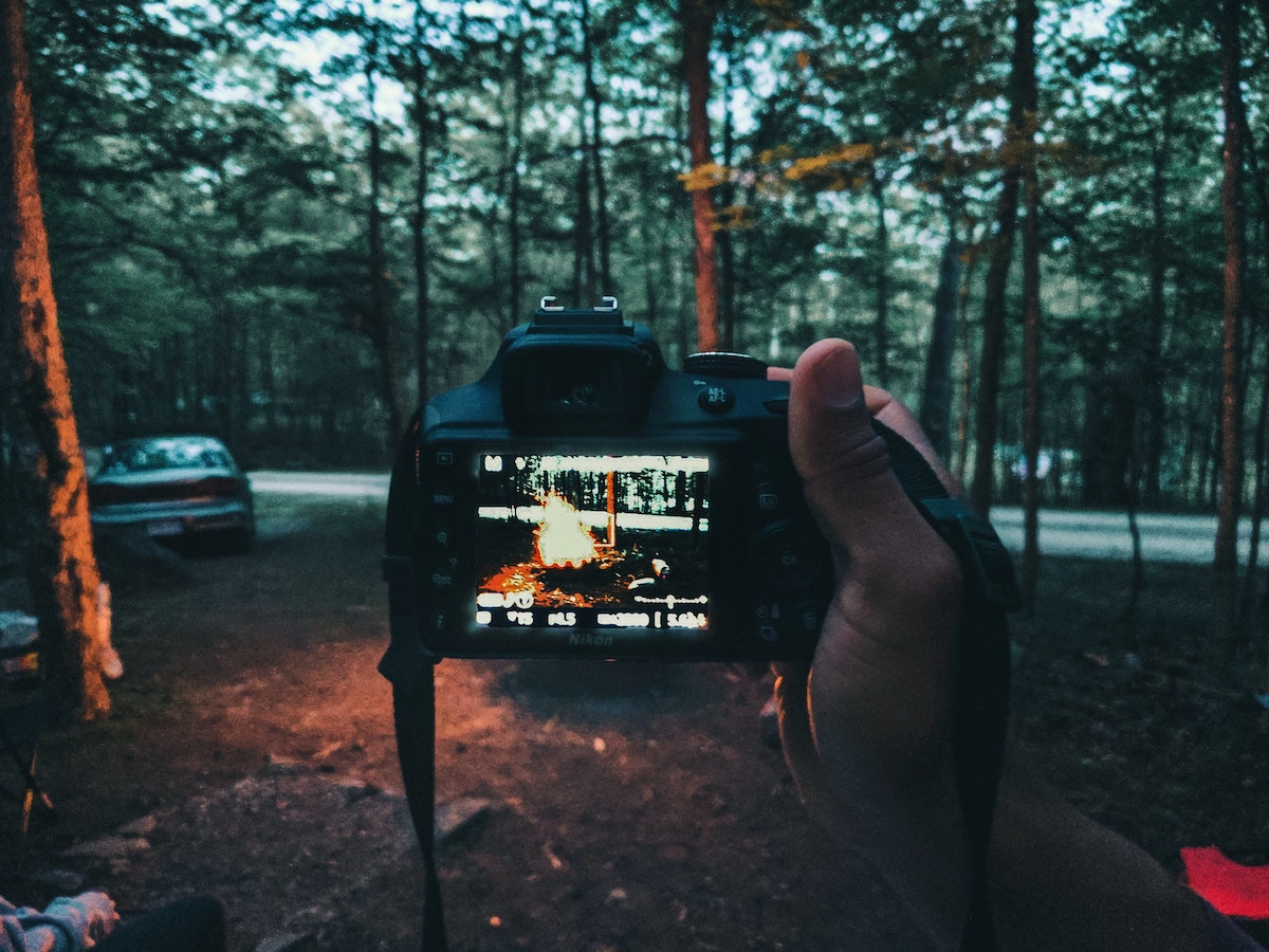 a hand holds a camera with a photo of a campfire on it