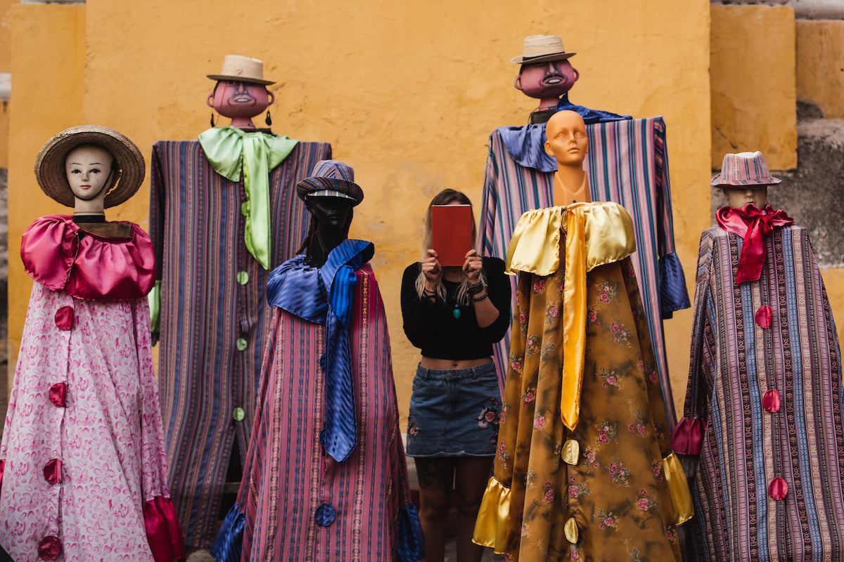 a girl stands in between 5 weird mannequins holding a wakeful travel journal over her face