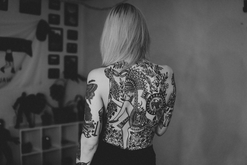 a blonde girl's back covered in travel tattoos