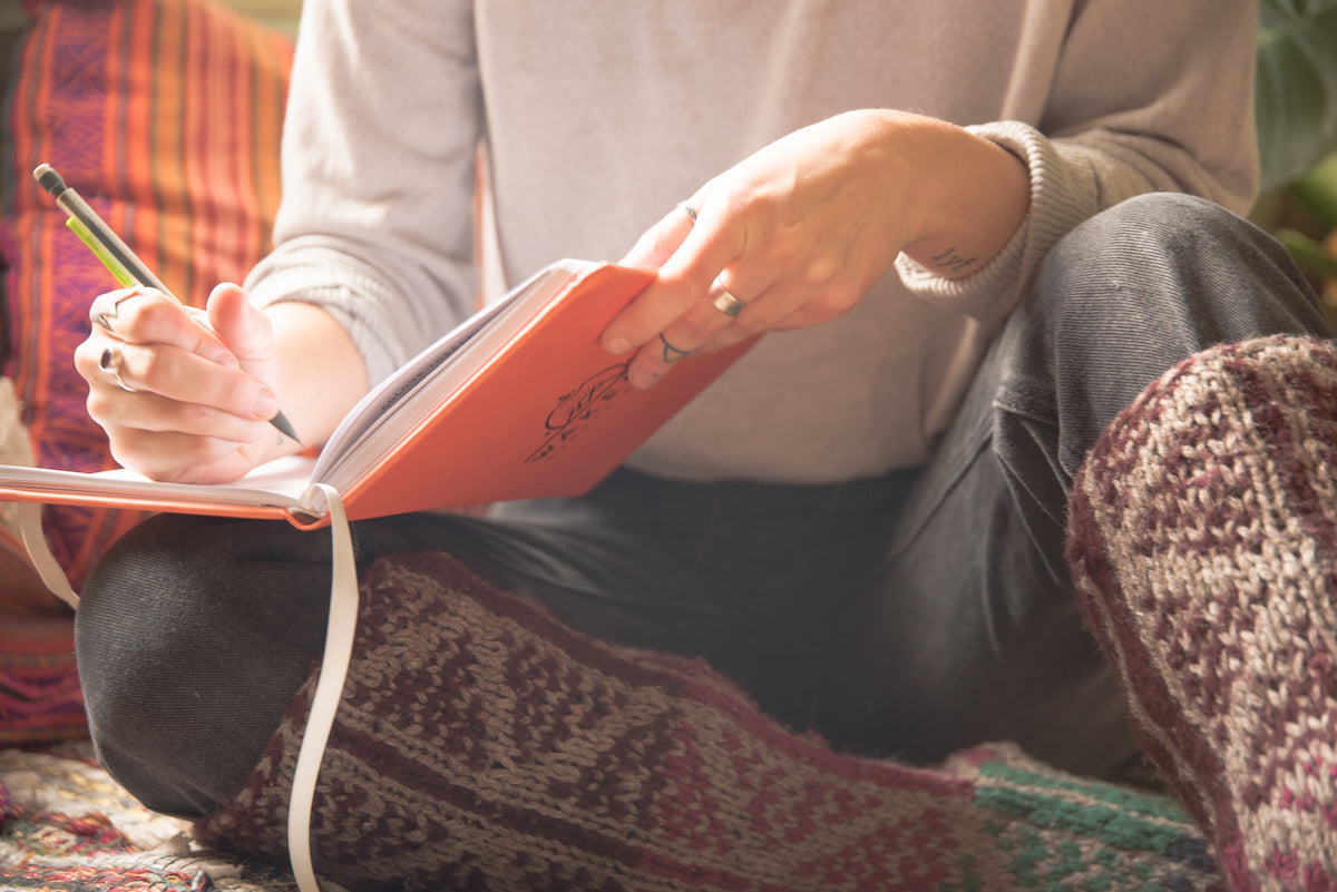 A girl in slippers writing in her mindful travel journal
