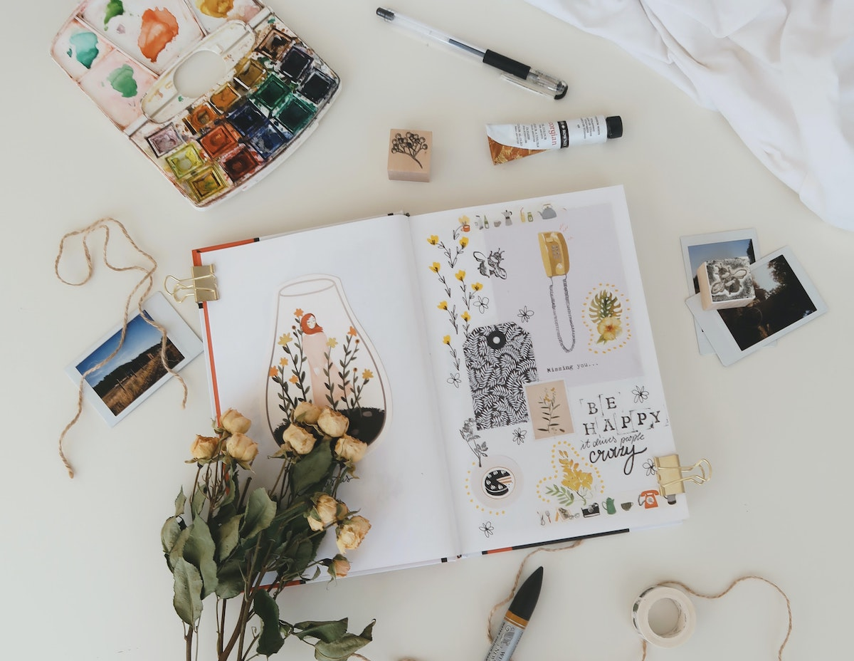 bullet journal laid out with paints and flowers around