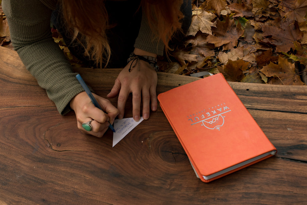 a girl writing on a triangle from the mindful travel journal