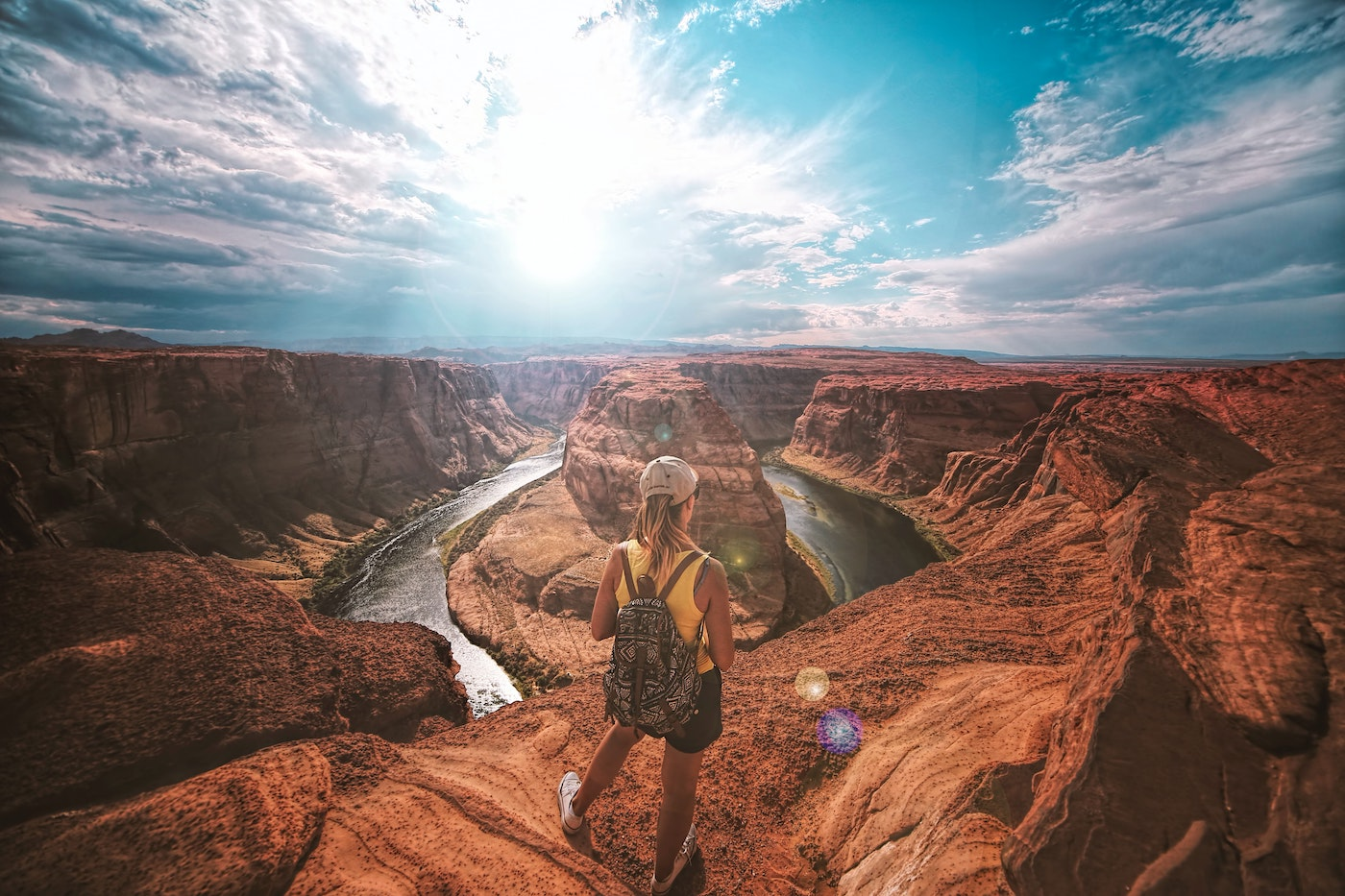 woman in utah hiking surrounded by red rocks